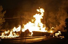 FILE - In this June 19, 2009 file photo, a car at right is seen engulfed in flames from rail cars loaded with ethanol that derailed in Rockford, Ill. A Rockford woman died as she tried to flee the derailment.  For two decades, one of the nation's most common types of rail tanker, known as a DOT-111, has been allowed to haul hazardous liquids from coast to coast even though transportation officials were aware of a dangerous design flaw that almost guarantees the car will tear open in an accident. The rail and chemical industries have committed to a safer design for new tankers, but they do not want to modify tens of thousands of existing cars. That's despite a spike in the number of accidents. (AP Photo/Rockford Register Star, Scott Morgan)  MANDATORY CREDIT