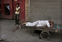 An Indian laborer sleeps on his trolley in the street in New Delhi, India, early Wednesday, Sept. 12, 2012. (AP Photo/Kevin Frayer)
