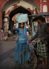 An Indian woman negotiates with a bicycle rickshaw puller in the street in New Delhi, India, early Wednesday, Sept. 12, 2012. (AP Photo/Kevin Frayer)