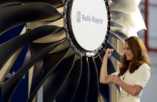 Britain's Kate, the Duchess of Cambridge, flexes her biceps after pushing in the last blade of a Rolls-Royce wide chord fan blade during her tour of the Rolls-Royce Seletar Campus on Wednesday, Sept. 12, 2012,  in Singapore. Prince William, the Duke of Cambridge and his wife Kate were the guests of honor at the official unveiling ceremony of the first Rolls-Royce Wide Chord Fan Blade and Trent aero engine to be produced in Singapore.(AP Photo / Bryan van der Beek)