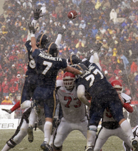 Provo - BYU defenders leap up, unsuccessfully attempting to block Utah's only score of the game, a field goal. BYU vs. Utah football Saturday at LaVell Edwards Stadium. Photo by Trent Nelson/The Salt Lake Tribune; 11/22/2003