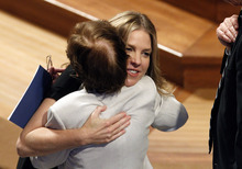 Singer Diana Krall hugs another guest at the Washington National Cathedral in Washington, Thursday, Sept. 13, 2012, following a national memorial service for the first man to walk on the moon, Neil Armstrong. (AP Photo/Ann Heisenfelt)