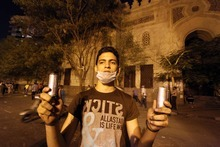 An Egyptian protester holds tear gas canisters fired during clashes between Egyptian police and protesters in front of the U.S. embassy in Cairo, Egypt ,Thursday, Sept. 13, 2012, as part of widespread anger across the Muslim world about a film ridiculing Islam's Prophet Muhammad.(AP Photo/Ahmed Gomaa)