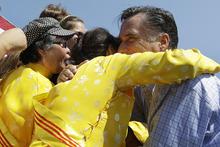 Republican presidential candidate, former Massachusetts Gov. Mitt Romney embraces women wearing traditional Vietnamese