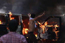 An Egyptian protester flashes the victory sign next to a burning police car during clashes near the U.S. embassy in Cairo, Egypt, Thursday, Sept. 13, 2012. Protesters clashed with police near the U.S. Embassy in Cairo for the third day in a row. Egypt's Islamist President Mohammed Morsi vowed to protect foreign embassies in Cairo, where police were using tear gas to disperse protesters at the U.S. mission. (AP Photo/Khalil Hamra)