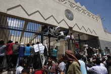 Yemeni protestors climb the gate of the U.S. Embassy during a protest about a film ridiculing Islam's Prophet Muhammad, in Sanaa, Yemen, Thursday, Sept. 13, 2012. Dozens of protesters gather in front of the US Embassy in Sanaa to protest against the American film