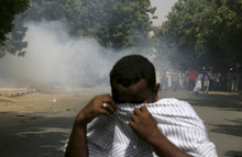 A Sudanese protester reacts to tear gas during a demonstration in Khartoum, Sudan, Friday, Sept. 14, 2012, as part of widespread anger across the Muslim world about a film ridiculing Islam's Prophet Muhammad. Germany's Foreign Minister says the country's embassy in the Sudanese capital of Khartoum has been stormed by protesters and set partially on fire. Minister Guido Westerwelle told reporters that the demonstrators are apparently protesting against an anti-Islam film produced in the United States that denigrates the Prophet Muhammad.(AP Photo/Abd Raouf)