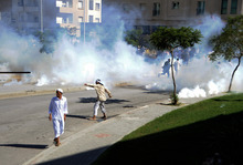 Demonstrators throw stones during a protest against the anti-Islam film