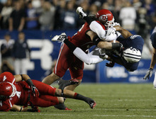 Trent Nelson | The Salt Lake Tribune  BYU wide receiver Ross Apo (11) is tackled by Utes linebacker Chaz Walker (32) and Utes linebacker Brian Blechen (4) (left) during BYU's game against Utah at Lavell Edwards Stadium in Provo, Utah September 17, 2011.