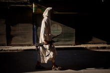 An FSA fighter walks through a street in the Bustan Al Qsar district in Aleppo, Syria, Wednesday, Sept. 12, 2012. (AP Photo/ Manu Brabo)
