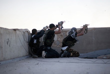 FSA fighters fire their weapons towards Syrian Army positions from the top of a building in the Izaa district in Aleppo, Syria, Wednesday, Sept. 12, 2012. The diplomat tasked with ending Syria's civil war said that the conflict is worsening on Thursday, the same day he travelled to the country for the first time since taking up a job he himself has called