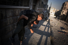 An FSA fighter carries a wounded comrade in the Izaa district in Aleppo, Syria, Wednesday, Sept. 12, 2012. (AP Photo/ Manu Brabo)