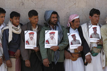 Relatives of soldiers who were killed in a car bomb attack targeting the motorcade of the country's defense minister hold their pictures during a funeral in Sanaa, Yemen, Thursday, Sept. 13, 2012.(AP Photo/Hani Mohammed)