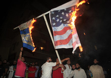 Lebanese Muslim protesters burn the American and Israeli flags during a protest about a film ridiculing Islam's Prophet Muhammad, in the southern port city of Sidon, Lebanon, Thursday, Sept. 13, 2012. (AP Photo/Mohammed Zaatari)