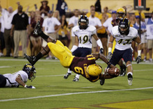 Arizona State running back Cameron Marshall, center, dives into the end zone for a touchdown against the Northern Arizona defense during the first half of their NCAA college football game on Thursday, Aug. 30, 2012, in Tempe, Ariz. (AP Photo/Rick Scuteri)