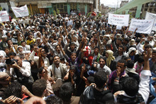 Protesters gather near the U.S. Embassy in Sanaa, Yemen, Friday, Sept. 14, 2012, as part of widespread anger across the Muslim world about a film ridiculing Islam's Prophet Muhammad. Arabic on a banner, right, reads,