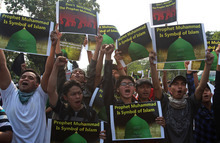 Indonesian Muslims shout slogans as they hold a banner which reads