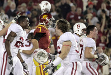 FILE - In this Oct. 29, 2012, file photo, Southern California quarterback Matt Barkley, center, looks on as Stanford football players celebrate their 56-48 win in triple overtime after an NCAA college football game in Los Angeles The secondary has become a weak spot for Stanford. And with Andrew Luck no longer around to match Barkley, the No. 21 Cardinal must find a way to slow No. 2 Southern California's passing game Saturday night in a rematch of last season's triple-overtime thriller. (AP Photo/Jae C. Hong)