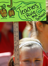 A young girl holds up a sign in support of striking Chicago school teachers during  a rally Saturday, Sept. 15, 2012, in Chicago. Union president Karen Lewis reminded the crowd that although there is a