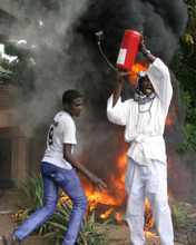 A Sudanese protester raises a fire extinguisher during a demonstration in Khartoum, Sudan, Friday, Sept. 14, 2012, as part of widespread anger across the Muslim world about a film ridiculing Islam's Prophet Muhammad. Germany's Foreign Minister says the country's embassy in the Sudanese capital of Khartoum has been stormed by protesters and set partially on fire. Minister Guido Westerwelle told reporters that the demonstrators are apparently protesting against an anti-Islam film produced in the United States that denigrates the Prophet Muhammad.(AP Photo/Abd Raouf)