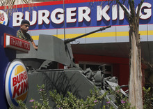 A Lebanese army soldier sits on his armored personnel carrier, as he stands guard outside the Burger King as part of stepped up security measures, in the southern port city of Sidon, Lebanon, Saturday Sept. 15, 2012. Security forces in Lebanon beefed up security presence around U.S. fast food restaurants Saturday, a day after a crowd angry over the anti-Islam movie set fire to a KFC and a Hardee's restaurant in Tripoli north of Lebanon, sparking clashes with police. At least one of the attackers was killed and 25 people wounded in the melee. (AP Photo/Mohammed Zaatari)