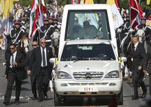 Pope Benedict XVI,  waves to the faithful from the popemobile as he is escorted by bodyguards upon his arrival at the Lebanese presidential palace, in Baabda east of Beirut, Lebanon, Saturday Sept. 15, 2012. Pope Benedict XVI has appealed for religious freedom in the Middle East, calling it fundamental for stability in a region bloodied by sectarian strife. The visit brings the pope to the nation with the largest percentage of Christians in the Mideast — nearly 40 percent of Lebanon's 4 million people, with Maronite Catholics the largest sect. (AP Photo/Hussein Malla)
