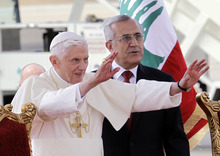 Pope Benedict XVI stands next to Lebanese President Michel Suleiman as he waves to the crowd at Rafik Hariri international airport, in Beirut, Lebanon, Friday, Sept. 14, 2012. Pope Benedict XVI arrived in Lebanon on Friday to urge peace at a time of great turmoil in the Middle East, saying the import of weapons to Syria during the country's civil war is a