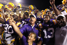 LSU head coach Les Miles center, sings the LSU alma mater with his daughter Macy Miles, below, and his team, after their NCAA college football game against Idaho in Baton Rouge, La. Saturday, Sept. 15, 2012. LSU won 63-14. (AP Photo/Gerald Herbert)