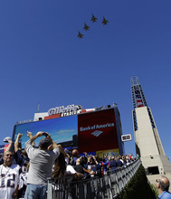 Fans photograph a military jet flyover before an NFL football game between the New England Patriots and the Arizona Cardinals, Sunday, Sept. 16, 2012, in Foxborough, Mass. (AP Photo/Elise Amendola)