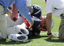 New England Patriots tight end Aaron Hernandez holds his right lower leg as he lies on the field in the first quarter of an NFL football game against the Arizona Cardinals, Sunday, Sept. 16, 2012, in Foxborough, Mass. (AP Photo/Elise Amendola)