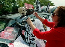 Philomena Johnson, a delegate from Little Village Academy, decorates her vehicle to highlight the need for increased social services in schools before attending a meeting of the Chicago Teachers Union delegates Sunday, Sept. 16, 2012 in Chicago. Hundreds of CTU delegates are expected to review a proposed contract and vote on whether to suspend the teachers strike which has kept more than 350,000 students out of school since Monday. (AP Photo/Sitthixay Ditthavong)