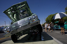 Kim Raff | The Salt Lake Tribune People walk past Patrick Evje's 1963 Chevrolet Impala convertible during the El Grito de la Independencia, Mexico's official independence day, festival and car show at Centro Civico Mexicano in Salt Lake City, Utah on September 16, 2012.