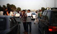 A Libyan follower of Ansar al-Sharia Brigades carries a placard reads in Arabic