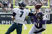 Philadelphia Eagles quarterback Michael Vick, left, throws an interception as Baltimore Ravens linebacker Courtney Upshaw pursues in the first half of an NFL football game on Sunday, Sept. 16, 2012, in Philadelphia. (AP Photo/Mel Evans)