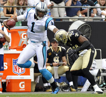 Carolina Panthers' Cam Newton (1) tries to run past New Orleans Saints' Roman Harper (41) during the first quarter of an NFL football game in Charlotte, N.C., Sunday, Sept. 16, 2012. (AP Photo/Rainier Ehrhardt)