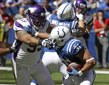 Indianapolis Colts' Donald Brown (31) runs out of a tackle of Minnesota Vikings' Kevin Williams (93) during the first half of an NFL football game in Indianapolis, Sunday, Sept. 16, 2012. (AP Photo/Darron Cummings)