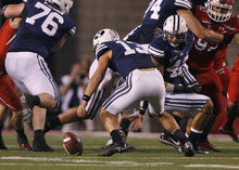 Scott Sommerdorf  |  The Salt Lake Tribune              Brigham Young Cougars quarterback Riley Nelson (13) reaches down to collect a fumble during first half play. BYU fumbled at least three times but lost none of them during the first half. Utah was tied with BYU 7-7 at the half, Saturday, September 15, 2012.