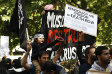 Islamic supporters outside the US Embassy in London during a protest against the US made anti-Muslim film purportedly denigrating the Prophet Mohammad, Friday, Sept. 14, 2012. Arabic on boy's scarf reads:
