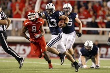Chris Detrick  |  The Salt Lake Tribune Brigham Young Cougars quarterback Riley Nelson (13) runs the ball past Utah Utes defensive end Nate Fakahafua (8) during the second half of the game at Rice-Eccles Stadium Saturday September 15, 2012.  Utah won the game 24-21.