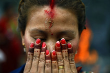 A Nepalese Hindu woman offers prayers at the Pashupatinath temple during Teej festival celebrations in Katmandu, Nepal, Tuesday, Sept. 18, 2012. During the festival, Nepalese Hindu women observe a day-long fast and pray for their husbands and for a happy married life. Those who are unmarried pray for a good husband. (AP Photo/Niranjan Shrestha)
