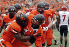 Oklahoma State quarterback J.W. Walsh (4) celebrates with running back Jeremy Smith, left, following a touchdown against Louisiana-Lafayette during the third quarter of an NCAA college football game in Stillwater, Okla., Saturday, Sept. 15, 2012. Oklahoma State won 65-24. (AP Photo/Sue Ogrocki)