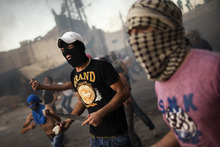 Masked Palestinians throw stones towards Israeli security forces, not pictured, during clashes erupted after demonstration against an anti-Islam film called