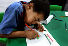 A Syrian boy, who fled his home with his family due to fighting between rebels and government forces, draws a military tank with the Syrian revolutionary flag, at the UNHCR nursery, in Baalbek, east of Lebanon, Tuesday, Sept. 18, 2012. There are more than 65,000 Syrian refugees in Lebanon living mostly in northern Lebanon and in the country's eastern Bekaa region. (AP Photo/Bilal Hussein)