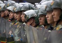A Chinese paramilitary policeman wipes his face while standing guard with his comrades during a protest against Japan in Chengdu in southwest China's Sichuan province Tuesday, Sept. 18, 2012. The 81st anniversary of a Japanese invasion brought a fresh wave of anti-Japan demonstrations in China on Tuesday, with thousands of protesters venting anger over the colonial past and a current dispute involving contested islands in the East China Sea. (AP Photo/Andy Wong)