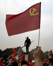 Chinese demonstrators wave national flags and Communist Party's flags in front of a people's hero statue on display at a park during an anti-Japan protest in Chengdu in southwest China's Sichuan province Tuesday, Sept. 18, 2012. The 81st anniversary of a Japanese invasion brought a fresh wave of anti-Japan demonstrations in China on Tuesday, with thousands of protesters venting anger over the colonial past and a current dispute involving contested islands in the East China Sea. (AP Photo/Andy Wong)