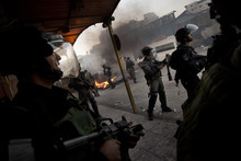 Israeli security forces take position during clashes with Palestinian stone-throwers, not pictured, in Shuafat refugee camp, Jerusalem, Tuesday, Sept. 18, 2012. Clashes erupted after a demonstration against an anti-Islam film called