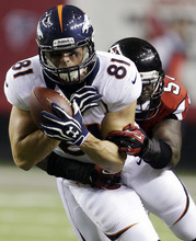 Denver Broncos tight end Joel Dreessen (81) makes a catch under pressure from Atlanta Falcons linebacker Akeem Dent (52) during the first half of an NFL football game, Monday, Sept. 17, 2012, in Atlanta. (AP Photo/David Goldman)