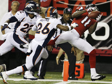 Atlanta Falcons wide receiver Julio Jones (11) cannot pull in a catch as Denver Broncos free safety Rahim Moore (26) and cornerback Tracy Porter (22) defend during the first half of an NFL football game, Monday, Sept. 17, 2012, in Atlanta. (AP Photo/David Goldman)
