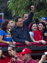 Venezuela's President Hugo Chavez, top, waves to supporters during a campaign rally in Propatria neighborhood, Caracas, Venezuela, Sept. 17, 2012. Venezuela's presidential election is scheduled for Oct. 7. (AP Photo/Ariana Cubillos)