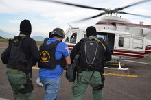 In this photo provided by the Ministry of Popular Power for Interior Relations and Justice, Venezuela's judicial police officers escort alleged Colombian drug trafficker Daniel Barrera, center, toward a helicopter at the Regional Command No. 1 National Guard base in San Cristobal, Tachira state, Venezuela, Wednesday, Sept. 19, 2012. Colombia's President Juan Manuel Santos announced Tuesday evening that a man he described as Colombia's last big-time drug lord had been captured in neighboring Venezuela. It was the third arrest of a purported Colombian drug boss in the last year. Santos said alleged drug boss Daniel